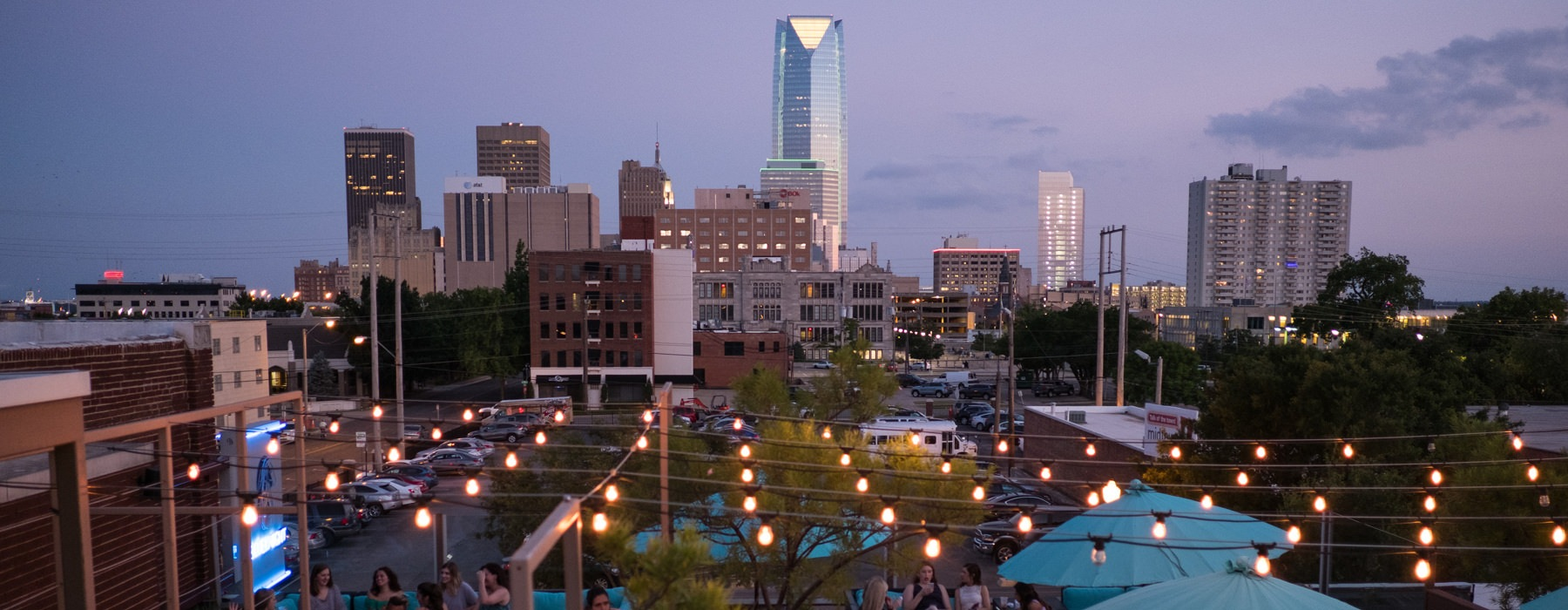 Oklahoma City skyline with people eating outside a neighborhood restaurant in the foreground